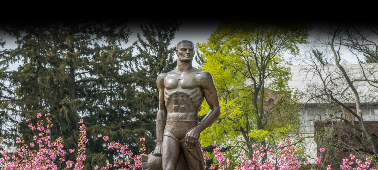 Sparty statue with spring trees